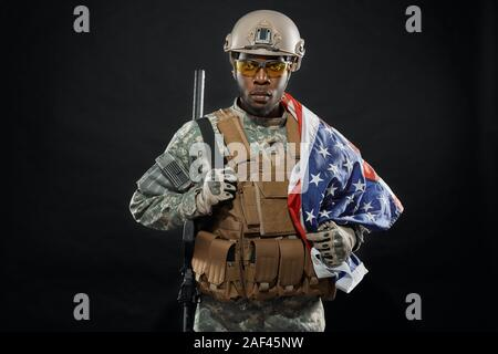 Front view of brave African soldier posing with national flag on shoulder and weapon. Seriously ranker wearing uniform, helmet and glasses looking at camera. Concept of army. - Stock Photo