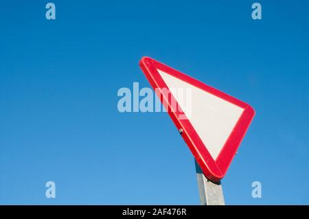 Give way signal against blue sky. - Stock Photo