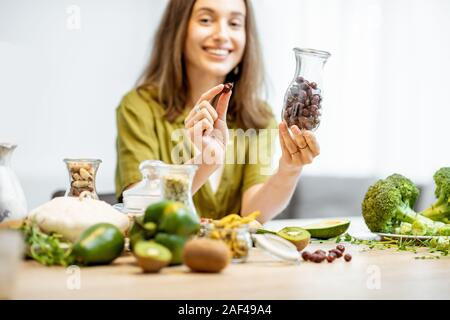 Portrait of a young cheerful woman with dried rosehip and lots of healthy green food on the table. Concept of vegetarianism and well-being - Stock Photo