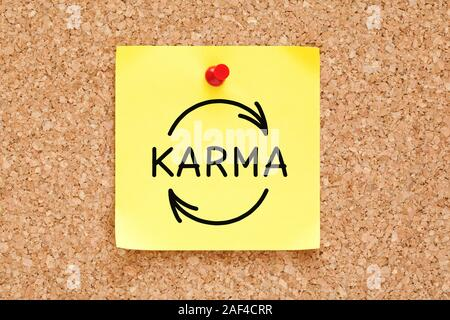 Hand drawing Karma cycle concept on yellow adhesive note pinned on cork bulletin board. - Stock Photo