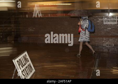 London, UK. 12th Dec, 2019. In the evening rain, voters stream to City of London Girls School, City of London's Ward of Cripplegate, to cast their vote in 2019 general election that will decide the next steps in Brexit, City of London, UK. Credit: Veronika Lukasova/ZUMA Wire/Alamy Live News - Stock Photo
