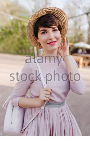 Lovely young woman with shiny short hair posing with pleasure during walk in park. Portrait of trendy girl wearing vintage attire and silver jewelry, standing outside with white backpack. - Stock Photo