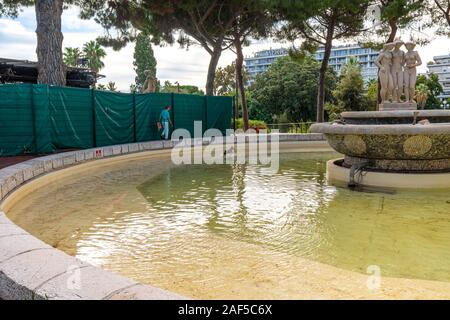 A woman watches as her small dog plays in the water at the Three Graces fountain in Albert Park on the French Riviera. - Stock Photo