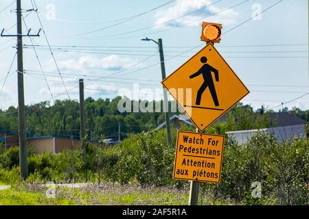 Warning for pedestrians, Warning road sign, Watch for pedestrians bilingual sign French and English, with yellow lamp, Canadian rural area background - Stock Photo