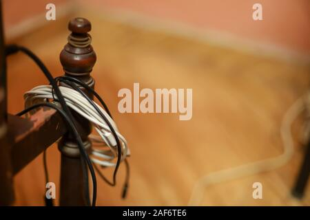 Smartphone cable or broken phone cable hangs on desks - Stock Photo