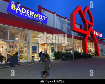 Offenbourg, Germany - Nov 11, 2019: Germany construction store Bauhaus with customer woman walking out of the store at dusk and Badewelt logotype - Stock Photo