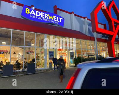 Offenbourg, Germany - Nov 11, 2019: Wide view of Germany construction store Bauhaus with customer woman walking out of the store at dusk and Badewelt logotype - Stock Photo