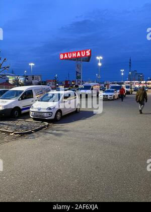 Offenbourg, Germany - Nov 11, 2019: Large parking of construction store Bauhaus with customers walking toward parked cars at dusk - Stock Photo