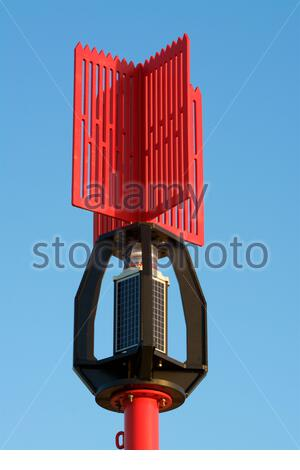 A red port navigation mark with solar panels - Stock Photo
