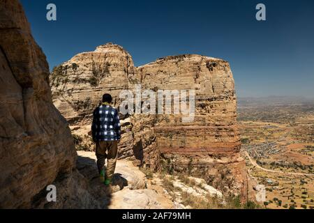 Ethiopia, Tigray, Gheralta Escarpment, Debre Maryam Korkor guide on ledge leading to Abba Daniel Korkor rock-cut church above Megab village - Stock Photo