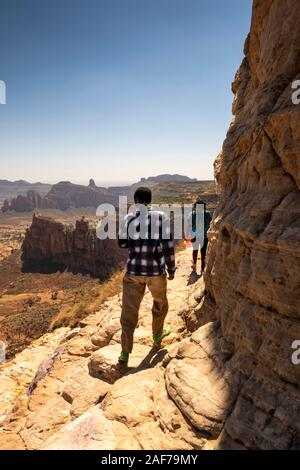 Ethiopia, Tigray, Megab, Gheralta Escarpment, Debre Maryam Korkor guides on ledge leading to Abba Daniel Korkor rock-cut church - Stock Photo