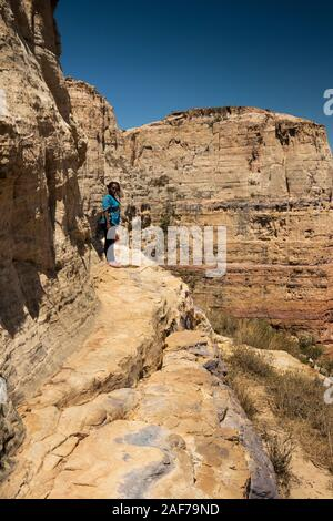 Ethiopia, Tigray, Megab, Gheralta Escarpment, Debre Maryam Korkor, female guide on ledge leading to Abba Daniel Korkor rock-cut church - Stock Photo