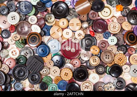 top view of pile of many different buttons close up on pink - Stock Photo