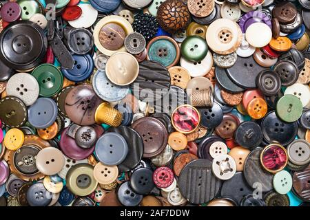 top view of heap of many different buttons close up on blue - Stock Photo