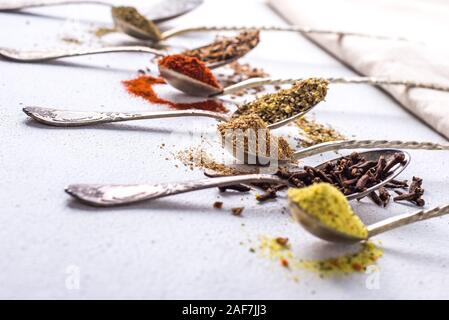 Various spices ground turmeric pepper ginger cinnamon herb seasoning salt paprika caraway seeds on the table. View from above. fragrant indian spices