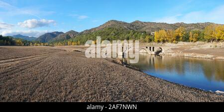 Spain, an old stone bridge in the reservoir of Boadella with a low water level, panoramic landscape, Catalonia, Girona province, Alt Emporda - Stock Photo