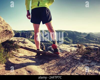 Male Sportsman in Running Shoes and Preparing for wild nature Run at Sunset. Healthy Lifestyle and Active Sport Concept - Stock Photo