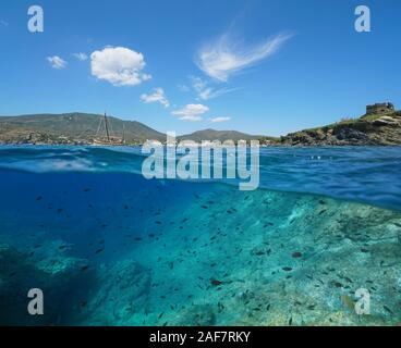 Spain, Mediterranean seascape near Cadaques, coastline with many fish in the sea, Costa Brava, split view over and under water surface, Catalonia