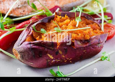 Baked sweet potatoes with butter. Vegetarian cuisine. Diet menu. - Stock Photo