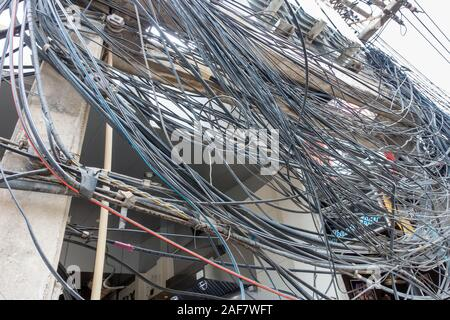 Chaotic electricity supply, hundreds of wires around poles - Stock Photo