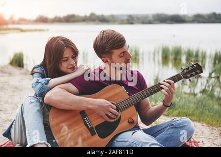 Man plays guitar for his girlfriend at beach on their picnic at daytime - Stock Photo