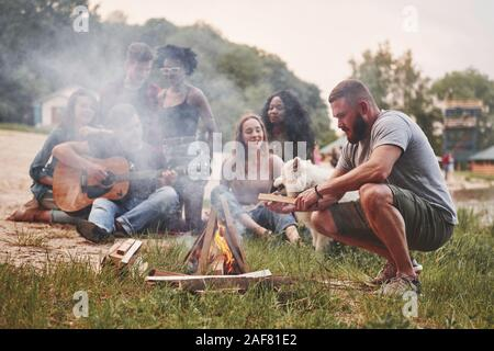 Too much smoke. Group of people have picnic on the beach. Friends have fun at weekend time - Stock Photo