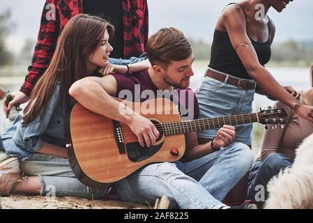 Concentrated at playing. Group of people have picnic on the beach. Friends have fun at weekend time - Stock Photo