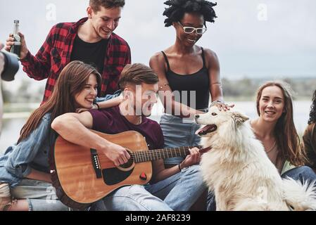New little friend in the company. Group of people have picnic on the beach. Having fun at weekend time - Stock Photo
