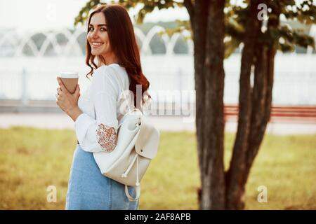 Fresh drink in hands. Young woman have good time in the park at her weekend - Stock Photo