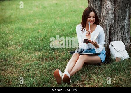 Holds pen and smiles. Young woman have weekend and sits in the park at daytime - Stock Photo