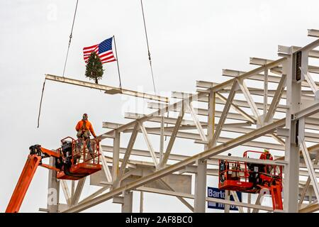 Detroit, Michigan USA - 13 December 2019 - Construction workers raise a flag and a Christmas tree on the last piece of structural steel to be placed on Fiat Chrysler's new automobile assembly plant. It is the first new assembly plant to be built in Detroit in 30 years. Credit: Jim West/Alamy Live News