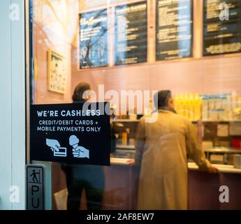 A sign on the door of a Van Leeuwen ice cream parlor in New York informs potential diners that the establishment does not accept cash, only debit and credit cards, seen on Tuesday, December 10, 2019. (© Richard B. Levine) - Stock Photo