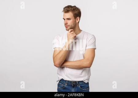 Thoughtful and creative good-looking male manager, designer decide what do, look away thinking, smiling pleased, have interesting idea, concept - Stock Photo