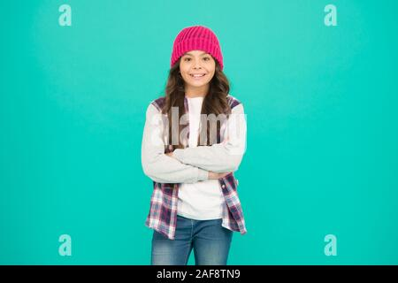 How cool am I. Kids fashion. Girl cute child wear knitted hat. Little girl wearing winter hat. Comfy and cool. Girl long curly hair wear hat. Must have street style accessory trends. Modern fashion. - Stock Photo