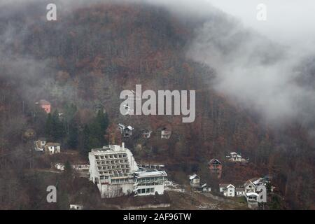 Old, abandoned, ruined hotel building, villas and houses next to the road in the misty mountain covered by colorful red trees - Stock Photo