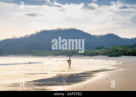A solo surfer on Ocotal beach, San Juan del Sur, Nicaragua - Stock Photo