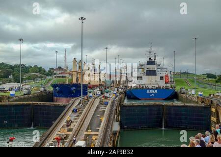 Panama - 11/6/19: A cruise ship with the passengers on the bow watching ships going through the busy Panama Canal. - Stock Photo