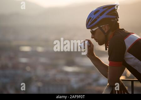 Adventure male Vloger Using Action Camera Outdoor. A male cyclist blogger shoots video on an action camera at sunset. Tourist Caucasian guy uses a - Stock Photo
