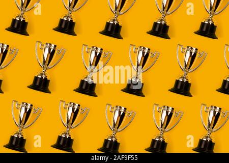 Champion cups on yellow background as pattern. Flat lay style. Open composition.