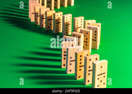 A curved line of standing wooden dominoes on solid green is seen lit from the right, producing long shadows falling on the left. The domino show is re - Stock Photo