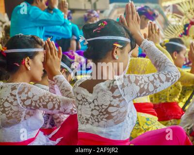 Ubud, Bali - Oct 12, 2012. A crowd of Hindu worshippers wearing traditional Balinese ceremonial clothing praying outdoors at a public temple. - Stock Photo