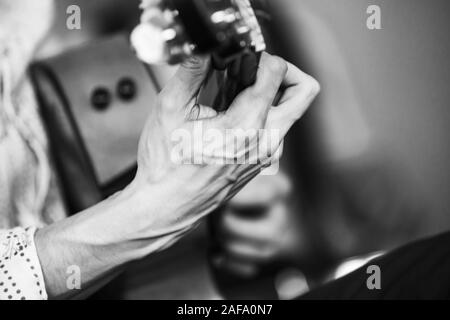 Live music background. Strong hand of an acoustic guitar player. Retro stylized black and white photo with selective focus