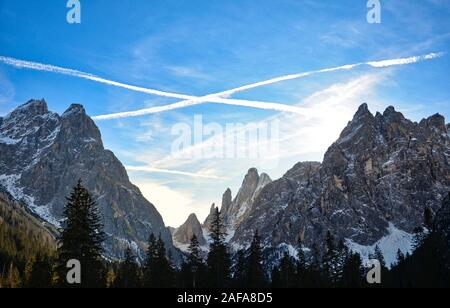 The trails left by the airplanes cross over the mountain peaks of the Val Fiscalina - Stock Photo