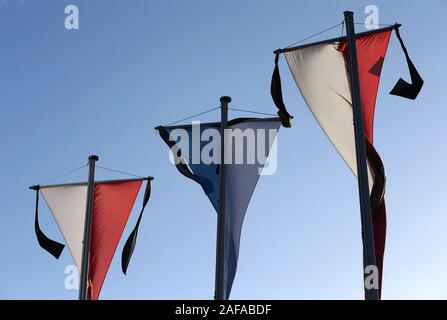 14 December 2019, Bavaria, Neusäß: Flags with a mourning pile stand in front of the parish church St. Ägidius at the funeral service for a killed firefighter. Photo: Karl-Josef Hildenbrand/dpa - Stock Photo