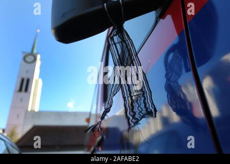 14 December 2019, Bavaria, Neusäß: A mourning pile is attached to the rear mirror of a fire truck, which stands in front of the parish church St. Ägidius during the funeral service for a killed fireman. Photo: Karl-Josef Hildenbrand/dpa - Stock Photo