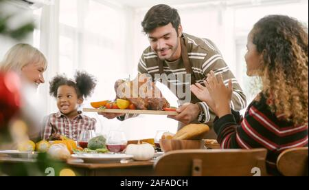 father carrying turkey served for family on thanksgiving dinner .Thanksgiving Celebration tradition concept - Stock Photo