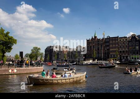 View of people riding open boats in Amstel river doing canal cruise tours. Historical, traditional and typical buildings are in the background. It is - Stock Photo