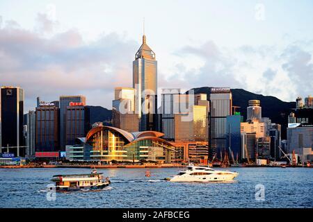 Blick von Kowloon bei Sonnenuntergang auf die Skyline auf Hongkong Island am Hongkong River, mit Booten auf dem Fluß, Central, mit dem International C - Stock Photo