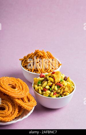 Indian Snack : Chakli, chakali or Murukku and Besan (Gram flour) Sev and chivada or chiwada on pink background. Diwali Food - Stock Photo