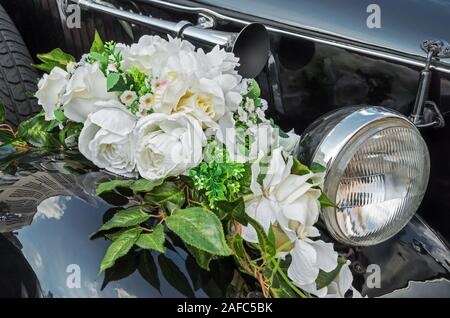 Wedding bouquet with a white roses lying on the  of a black vintage automobile - Stock Photo